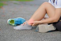 la femme de forme physique tenant sa blessure à la jambe de sports, muscle douloureux pendant la formation photos stock