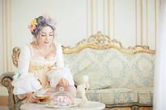 La femme de Greyhead dans les rococos habillent la pose devant le fond rose tout en buvant du thé image stock