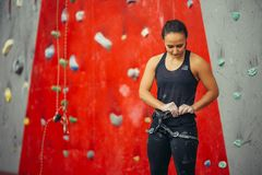 La femme de grimpeur met le harnais assiégeant dessus pour la pratique sur le mur artificiel de roche image stock