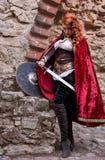 La femme de guerrier avec l'épée dans des vêtements médiévaux est très dangereuse Images libres de droits