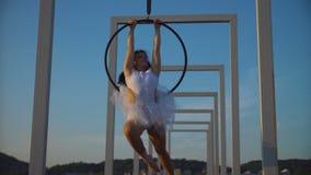 La femme de gymnastique d'air exécute des tours d'acrobaties sur le cercle aérien banque de vidéos