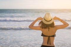 La femme de l'Asie avec le chapeau et le bikini sur la mer échouent photo libre de droits
