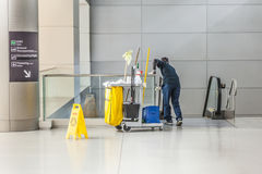 La femme de ménage avec son chariot à nettoyage nettoie le verre d'un St Images stock