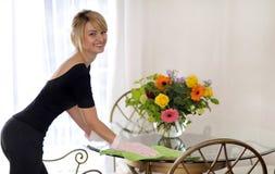 La femme de ménage dans les gants s'approchent de la table photo stock