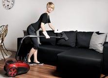 La femme de ménage nettoie à l'aspirateur le divan photos libres de droits