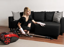 La femme de ménage nettoie à l'aspirateur le divan images libres de droits