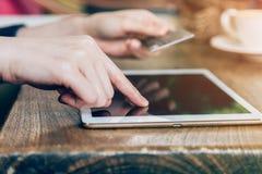 La femme de main paye par la carte de crédit l'achat en ligne sur un comprimé Photos libres de droits