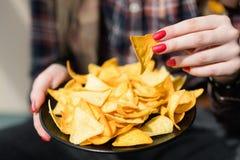 La femme de mauvaise habitude de casse-croûte d'aliments de préparation rapide mangent des frites photo stock
