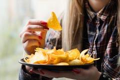 La femme de mauvaise habitude de casse-croûte d'aliments de préparation rapide mangent des frites photos libres de droits
