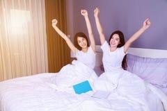 La femme de meilleur ami avec des bras a augmenté sur le lit dans la chambre à coucher Photographie stock