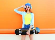 La femme de mode avec une planche à roulettes écoute la musique au-dessus de l'orange colorée Photo stock