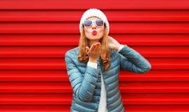 La femme de mode soufflant les lèvres rouges envoie un baiser d'air sur le fond photo libre de droits
