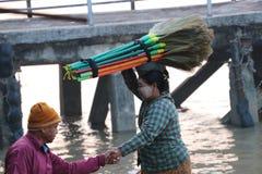 La femme de Myanmese avec la poudre de Myanmar de thanakha sur son visage a mis le balai main dans la main sur son chef et l'homm photos stock