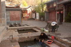 La femme de Naxi de Chinois lavant sur la piscine antique est dragon de cheval blanc. image stock