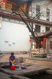 La femme de Naxi de Chinois lavant sur la piscine antique est dragon de cheval blanc. images libres de droits