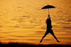 La femme de parapluie sautent et coucher du soleil dans le lac Photographie stock libre de droits
