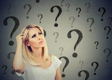La femme de pensée confuse par portrait déconcertante rayant la tête cherche une solution regardant beaucoup de points d'interrog image stock