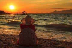 La femme de pensée s'asseyent dans le coucher du soleil sur la plage Images stock