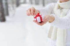 La femme de plan rapproché tient dans des ses mains le cadeau et commence à l'ouvrir Photographie stock libre de droits