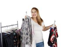 La femme de poids excessif tient beaucoup de vêtements Photos libres de droits