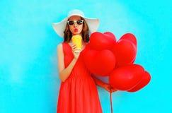 La femme de portrait dans le chapeau d'été boit du jus de la tasse avec le rouge des ballons à air Photographie stock