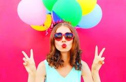 La femme de portrait dans un chapeau d'anniversaire souffle des prises de lèvres les ballons colorés d'un air sur le fond rose Photo stock