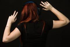 La femme de roux avec les écouteurs bleus danse photo stock