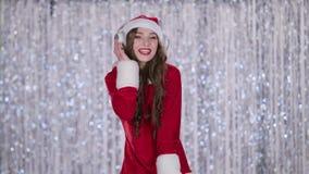 La femme de Santa chante des chansons de Noël dans des ses écouteurs Fond de Bokeh Mouvement lent banque de vidéos