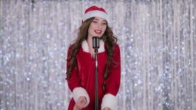 La femme de Santa dans le costume chante des chansons dans un rétro microphone Fond de Bokeh Mouvement lent banque de vidéos