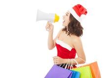 La femme de Santa de Noël à l'aide d'un mégaphone avec le cadeau met en sac Photographie stock