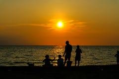 la femme de silhouette donnent la nourriture à la famille sur le coucher du soleil de plage Photos libres de droits