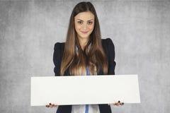 La femme de Smilingbusiness tient un endroit pour votre annonce Photographie stock libre de droits