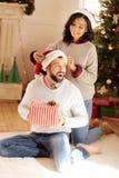 La femme de soin fixant le chapeau de Santa sur des maris se dirigent Photos stock