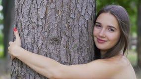 La femme de sourire étreint un arbre souriant, joie de la vie, nature d'amour, protection de l'environnement clips vidéos