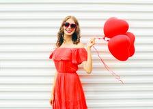 La femme de sourire assez heureuse dans la robe rouge et les lunettes de soleil avec le coeur de ballons à air forment la marche  Photo libre de droits