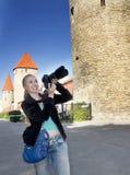 La femme de sourire avec l'appareil-photo photographie de vieilles tours de mur de ville Tallinn, Estonie Photos libres de droits