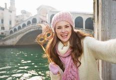 La femme de sourire avec le masque de Venise près de Rialto jettent un pont sur prendre le selfie Image libre de droits