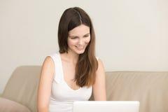 La femme de sourire communique avec l'ami dans l'Internet Image stock