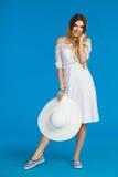 La femme de sourire d'été tient le chapeau blanc et regarder de Sun l'appareil-photo Photos libres de droits
