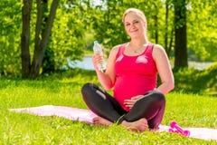 La femme de sourire dans la grossesse en retard fait le yoga Photos stock