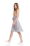 La femme de sourire dans la robe et des espadrilles blanches d'été marche Photos stock