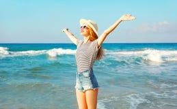 La femme de sourire heureuse apprécie l'odeur fraîche de la mer, jour d'été ensoleillé Images stock