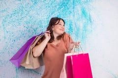 La femme de sourire heureuse aux achats tient les sacs en papier colorés, packa Photos libres de droits