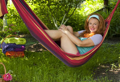 La femme de sourire heureuse se situe en nature de repos d'hamac Photos libres de droits