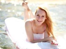 La femme de sourire heureuse se trouve sur un lit d'eau dans le jour d'été image libre de droits