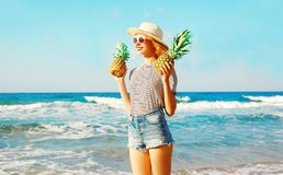 La femme de sourire heureuse tient deux ananas au-dessus de fond de mer Images libres de droits