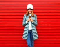 La femme de sourire de mode utilise le smartphone sur le fond rouge Photographie stock libre de droits