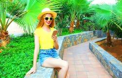 La femme de sourire de mode utilise un smartphone sur des palmiers Image stock