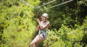 La femme de sourire montant une fermeture éclair rayent dans une forêt tropicale luxuriante photographie stock