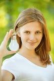 La femme de sourire montre la lampe à incandescence Images stock